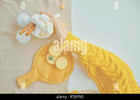 Femme dans un chandail jaune est titulaire d'un chocolat chaud avec de la guimauve et de la cannelle, également sur la table des cookies et un arbre de Noël miniature Banque D'Images