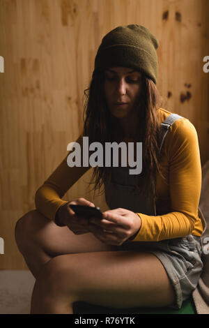 Woman using mobile phone in workshop