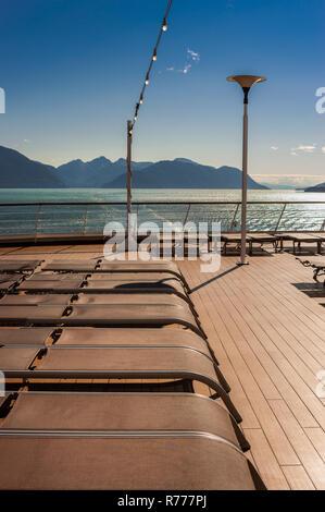 Rangée de marron en plastique vide réduit bateau de croisière, des chaises longues, en raison de forts vents, le pont Lido à l'arrière. Le contre-jour d'une journée ensoleillée, près de Juneau, Alaska, États-Unis Banque D'Images