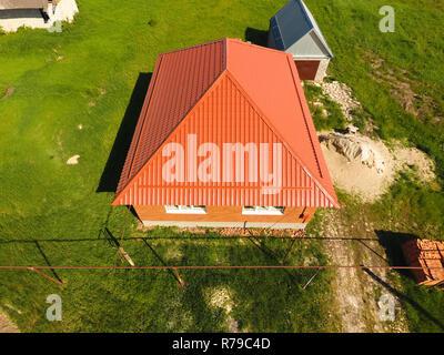 Maison avec un toit orange en métal, vue d'en haut. Profil métallique ondulé peint sur le toit. Banque D'Images