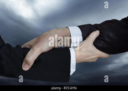 Des gestes avec les mains: avant-bras qui sont assemblées, un avant-bras de l'homme et la femme l'avant-bras. Aider les uns les autres dans le monde des affaires. Banque D'Images
