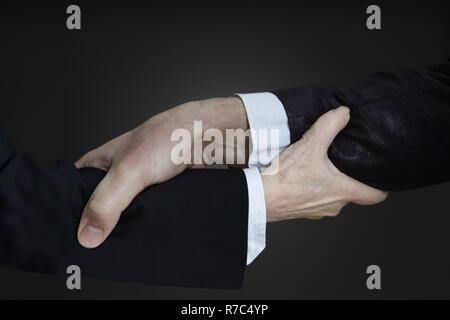 Des gestes avec les mains: avant-bras qui sont assemblées, un avant-bras de l'homme et la femme l'avant-bras. Aider les uns les autres dans le monde des affaires. Touche Bas Banque D'Images