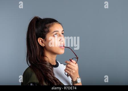 Cute girl de réfléchir avec les lunettes à la main, vue latérale du Brunette avec dans l'espace Banque D'Images
