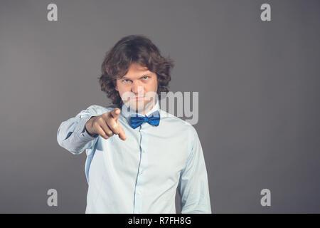 Jeune homme en chemise bleue avec papillon avec des cheveux hirsutes, doigt pointant directement vers l'appareil photo avec l'index, vous blâme en faisant de mauvaises choses sur un fond gris. Hey you. Studio shot. Banque D'Images
