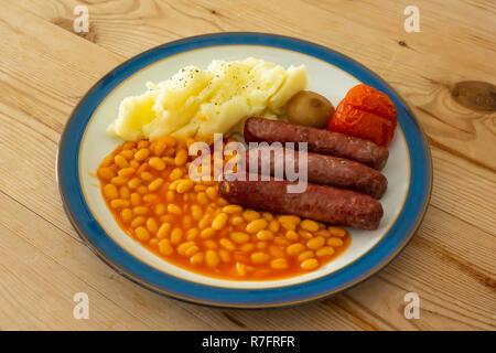 Un Yorkshire repas de saucisses, haricots, tomates grillées, purée de pommes de terre et un oignon mariné sur une plaque légèrement bleu sur une table en bois Banque D'Images