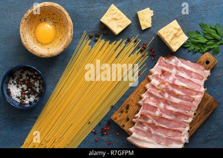 Ingrédients pour la cuisson des pâtes carbonara sur fond bleu, spaghetti, jambon, fromage, oeufs, épices. Haut de la vue, télévision lay Banque D'Images