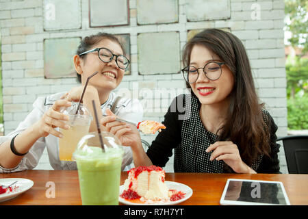 Deux asian woman bonheur émotion eating strawberry cheese cake in cafe Banque D'Images
