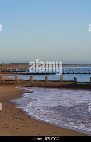 Ligne de plage en bois épis le long de la plage d''Aberdeen sur une calme, Ciel Soirée d'automne. L'Écosse, au Royaume-Uni.