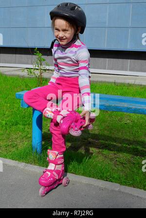 Une Fille en rose jean et un t-shirt à rayures dans un rouleau casque sur la tête et des rouleaux sur ses jambes est assis sur un banc le long d'une journée d'été. Phot