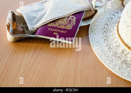 Les choses pour se rendre à l'étranger passeport biométrique britannique dans un portefeuille avec les chapeau sur un dessus de table. En Angleterre, Royaume-Uni, Angleterre Banque D'Images