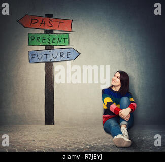 Jeune femme assise sur le sol en regardant un panneau avec des flèches qui montre le passé, le présent et le futur. Perdu dans le temps pittoresque route signe, destin evolu Banque D'Images