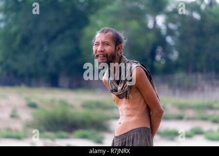 Don Daeng, Laos - 27 Avril 2018: Shirtless man walking local principal grâce à une plage dans une île éloignée de la rivière Mékong au Laos Banque D'Images