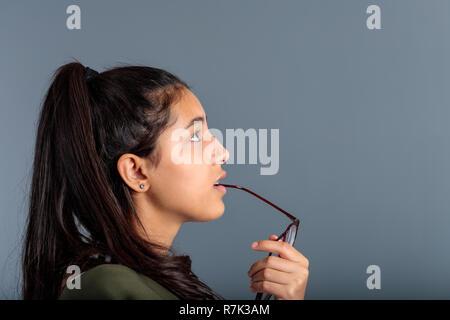 Teenage girl méditer avec lunettes poignée en vue de profil, la bouche brune dans l'espace Banque D'Images