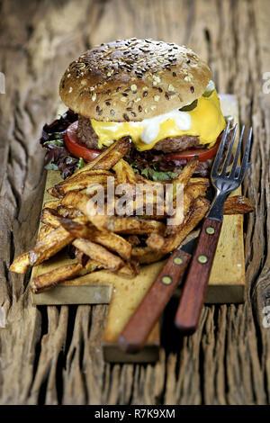 Cheeseburger et frites maison rustique sur fond de bois Banque D'Images