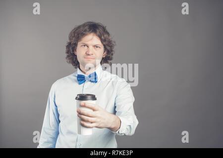 Portrait of happy bel homme en chemise bleue et cravate d'arc avec tasse de papier de café du matin. Bon matin avec du thé. Café à emporter, le temps d'une pause-café. Garçon de café propose d'aller. Tonique. Copy space Banque D'Images