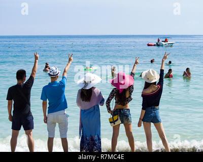 Silhouettes et groupe de cinq personnes debout asiatique sur fond de coucher de soleil sur la plage vide. Vacances Voyage ou la mer et la famille, concept friendshi Banque D'Images