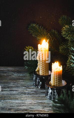 Brûler des bougies de cire et branches de sapin sur une vieille table en bois. Noël arrière-plan foncé. Copier l'espace.