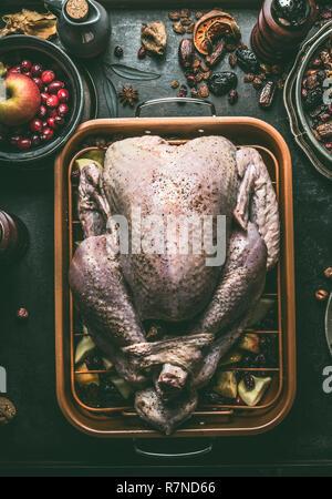 Matières dinde entière farcie aux fruits secs et pommes dans la rôtissoire sur arrière-plan foncé table de cuisine , vue d'en haut. Préparation Cuisson pour Thanksgivin Banque D'Images