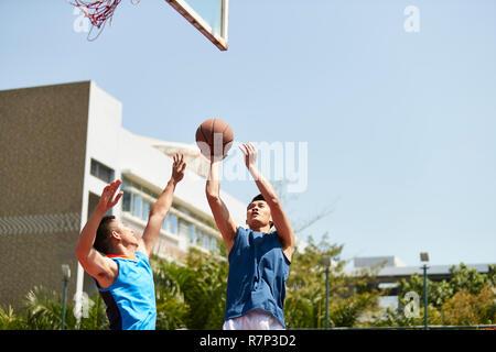 Young Asian basket-ball tir de la balle plus humains à l'extérieur sur cour. Banque D'Images