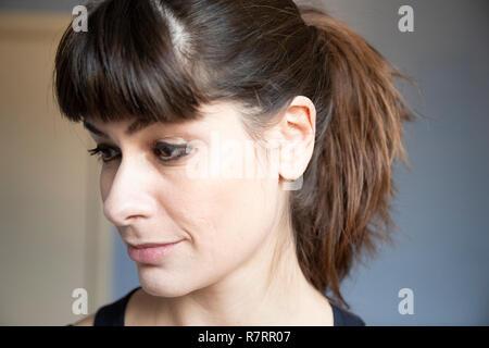 Jeune femme de trois quarts close-up portrait. Portrait avec de longs cheveux bruns dans ponytailand bangs. Expression souriante, à la recherche vers le bas. Banque D'Images