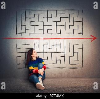Casual young woman sitting on the floor trouver une solution pour résoudre le problème et s'échapper de labyrinthe. D'enfreindre les règles, comme une flèche rouge pierce le m Banque D'Images