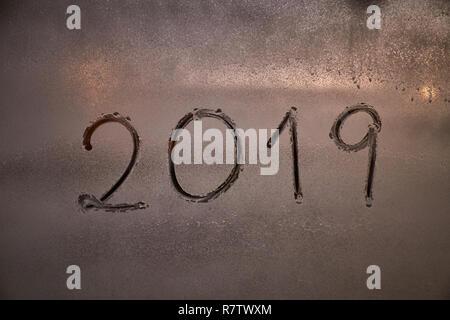 Écrit le numéro de la nouvelle année 2019 sur une fenêtre à l'aide d'un jet de mousse dans la nuit à la lumière de l'éclairage Banque D'Images