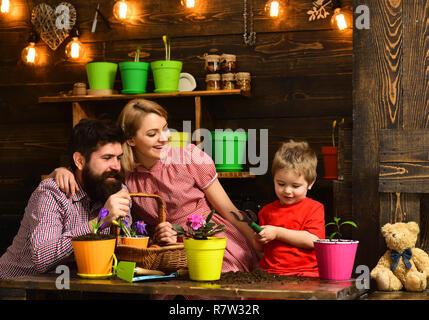 Concept de replantation. Peu de fils avec la mère et père de replanter en pot de fleurs. Mère et père de l'enfant avec la replantation houseplant sol en noir ou de saleté. Préparation pour la replantation Banque D'Images