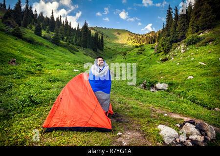Séjour touristique en sac de couchage près d'orange tente dans les montagnes du Kazakhstan, de l'Asie centrale Banque D'Images