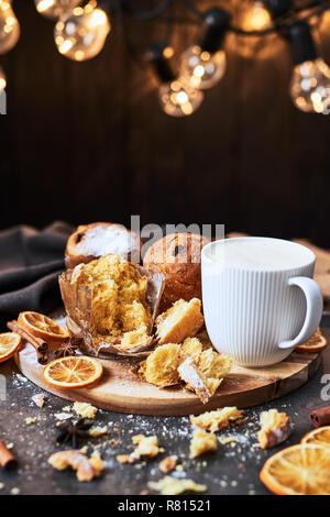 Panettone de Noël traditionnel avec des raisins secs et les fruits secs avec du lait chaud ou lait de poule sur une assiette de service en bois entouré par des miettes sur la table en béton o