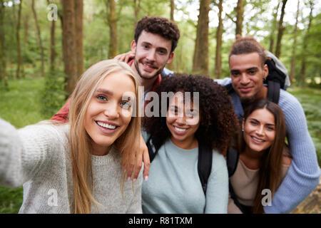 Groupe ethnique Multi de cinq jeunes amis adultes prendre un dans une forêt selfies lors d'une randonnée pédestre, portrait Banque D'Images