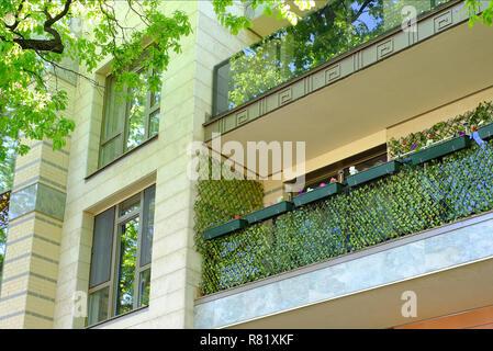 L'été une maison de pension. Les balcons dans les végétaux à fleurs. Marcher dans l'ombre fraîche des arbres. Senior Couple In Park Banque D'Images