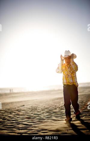 Jeune garçon portant un chapeau de cowboy en marchant le long d'une plage de sable fin au soleil. Banque D'Images