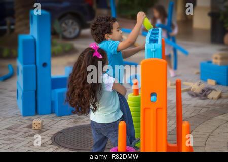 Grande soeur aide un jeune frère en lui tandis qu'il insère l'essorez vert dans les méga-brancher quatre-jeu, alors que d'autres enfants jouent. Banque D'Images