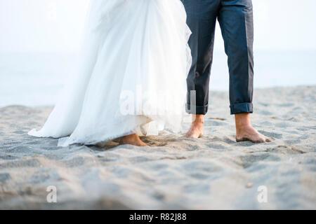 Les pieds nus jeunes mariés debout sur la plage Banque D'Images