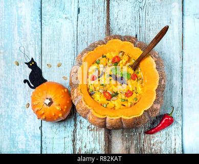 Avec la soupe de lentille dans la citrouille sculptée et black cat jouet sur le fond en bois bleu à Halloween party Banque D'Images