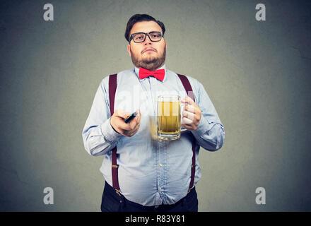 L'homme obèse paresseux adultes en tenue officielle holding mug de bière et regarder la télé sur fond gris Banque D'Images