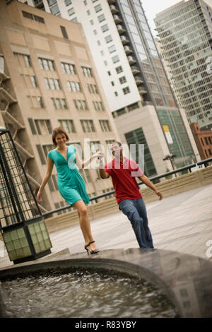 Jeune homme tenant la main de sa petite amie qu'elle marche le long du mur d'une fontaine. Banque D'Images