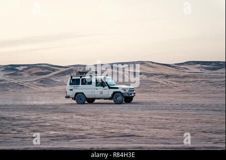 Hurghada, Egypte - 26 Février 2017: la conduite en jeep dans le désert de dunes de sable blanc sur fond de ciel. Safari tour. L'activité extrême. Les vacances et les voyages. Wanderlust Banque D'Images