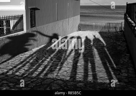 Les ombres de l'après-midi longue de sept personnes debout en face d'une plate-forme d'observation à Corfou, l'île de Kerkira, Grèce et la mer derrière la f métallique Banque D'Images