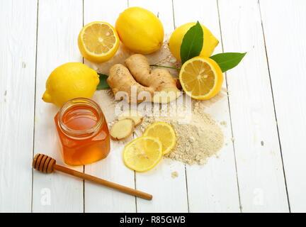 Racine de gingembre, citron et miel sur fond de bois blanc