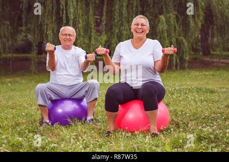 L'exercice aîné - Pensionné Smiling couple holding dumbbells, assis sur fitness ball in park Banque D'Images