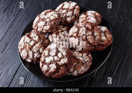 Close-up of Chocolate Crinkle cookies. 12.2005 biscuits au chocolat. Biscuits au chocolat, biscuits de Noël sur une plaque noire sur une table en bois, vue à partir de Banque D'Images