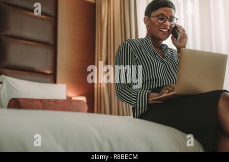Mature habillé formel Woman talking on mobile phone alors qu'il était assis dans la chambre d'hôtel à l'aide d'ordinateur portable. African businesswoman en tournée à partir d'un bain