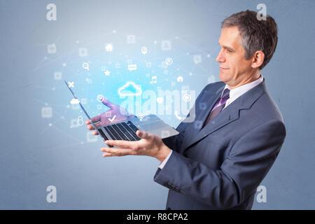 Man holding laptop projection de notifications, des symboles et de l'information basée sur un système de technologie de l'informatique en nuage Banque D'Images