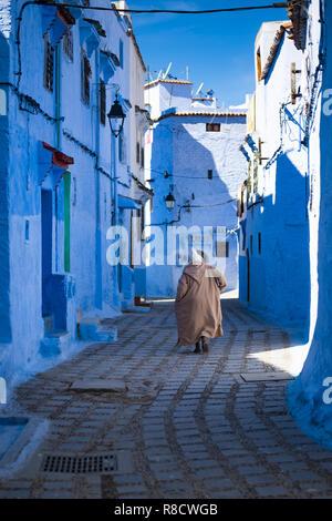 Un homme avec une robe traditionnelle marche dans la belle bleue médina de Chefchaouen, Maroc.
