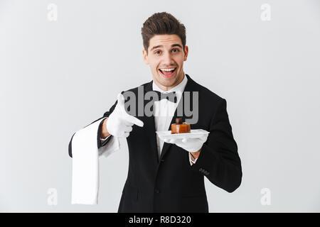 Beau jeune garçon en smoking avec bowtie maintenant la plaque de gâteau avec plus isolé sur fond blanc