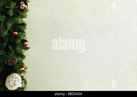Guirlande de Noël avec des branches de sapin et boules blanches rouge sur l'arrière-plan d'un mur beige clair à utiliser comme arrière-plan. Banque D'Images