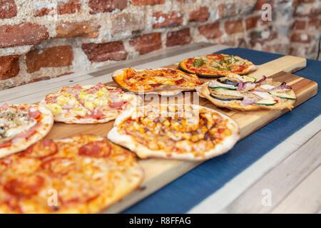 Sept petites pizzas sur une planche en bois, fraîchement sorti du four, prêt à manger sur un restaurant. avec l'accent dans les légumes de la pizza. Sur une table en bois avec un bl Banque D'Images
