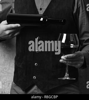 Barman sert verre à vin rouge. Garçon se verse dans un verre de vin rouge à partir de la bouteille. La main des hommes est titulaire d'une bouteille de vin sur fond mur beige. Service et boissons restaurant concept. Banque D'Images