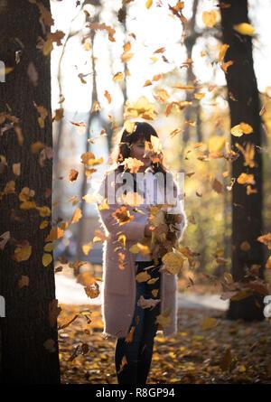 La jeune fille se tient dans le cadre de l'automne les feuilles qui tombent dans le parc Banque D'Images
